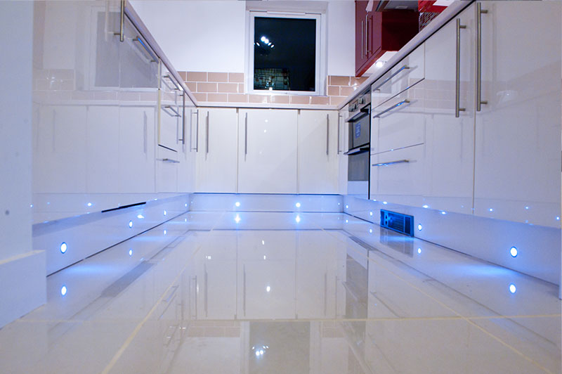 A modern kitchen with floor lights in a new build flat.